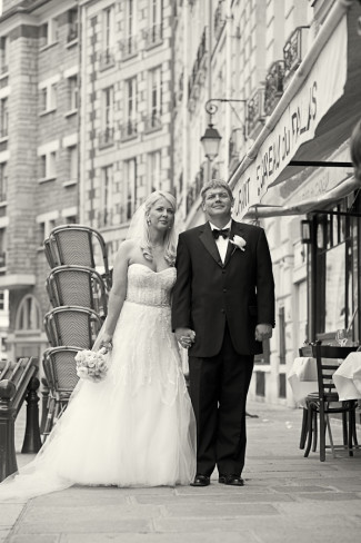 Bride and groom holding hands and walking the streets of Paris France