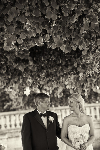 Bride and groom standing under a leafy tree looking at each other after elopement