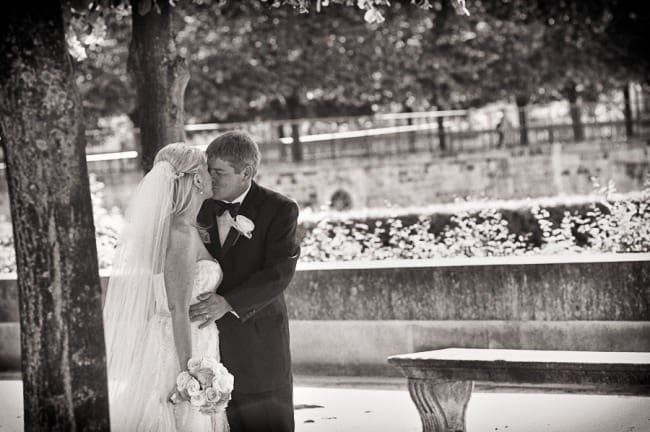 black and white photo of bride and groom kissing beside a tree in Paris after elopement