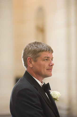 groom waiting at alter wearing black tux and white boutonniere