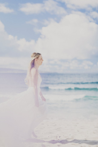 bride arriving on sandy beach with waves in background