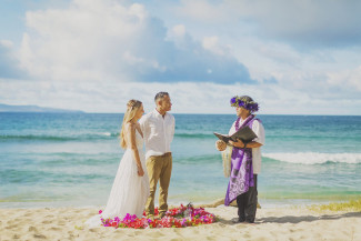 Kahu officiant reading vows on Ironwoods Beach