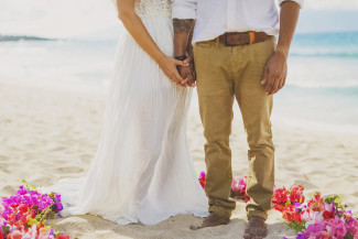 bride and groom stand barefoot on sandy Ironwoods Beach in Maui