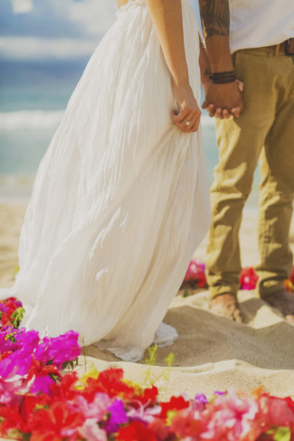 bride and groom hold hands inside ring of flowers on Ironwoods Beach