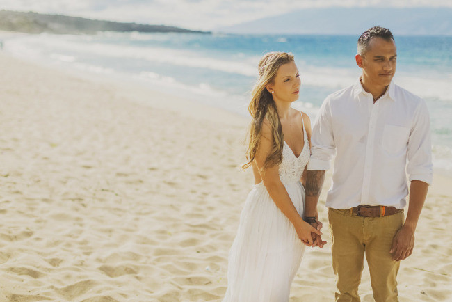 casual bride and groom on sandy beach in Maui