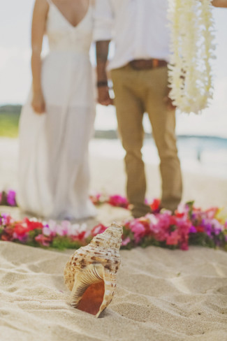 conch shell in foreground with bride and groom in background