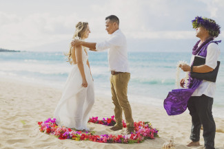 groom gives bride a lei inside ring of flowers