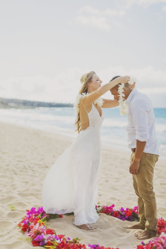 bride places white orchid lei on groom