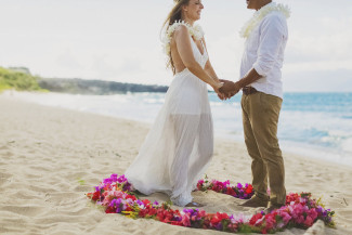 newlyweds hold hands inside Hawaiian circle of love flowers