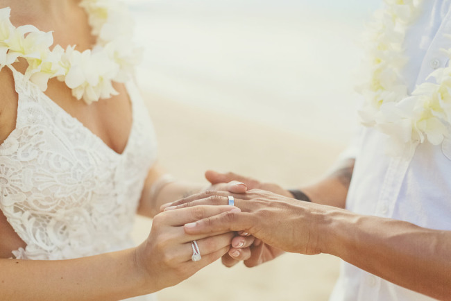 bride placing wedding band on groom's finger