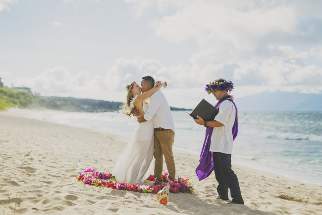 officiant standing nearby while bride and groom kiss