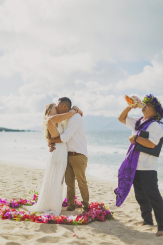 kahu blowing conch shell, bride and groom kiss inside ring of flowers