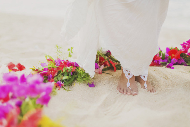 barefoot bride on white sand beach in Maui with colorful flowers
