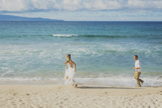Bride and groom run on sandy beach