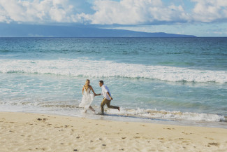 groom chasing bride on sandy Ironwoods Beach