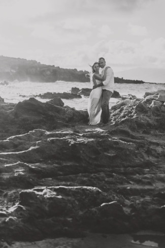 black and white photo of couple embracing on rocks in Maui