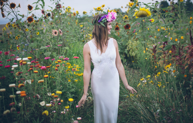 bride model walks through wild flowers
