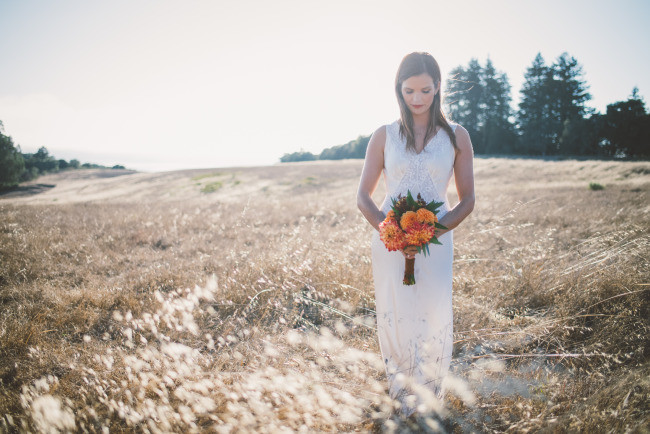 bride model with colorful bouquet in rustic field