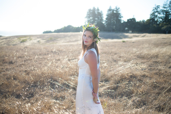 model with wedding gown and flower crown in rustic field