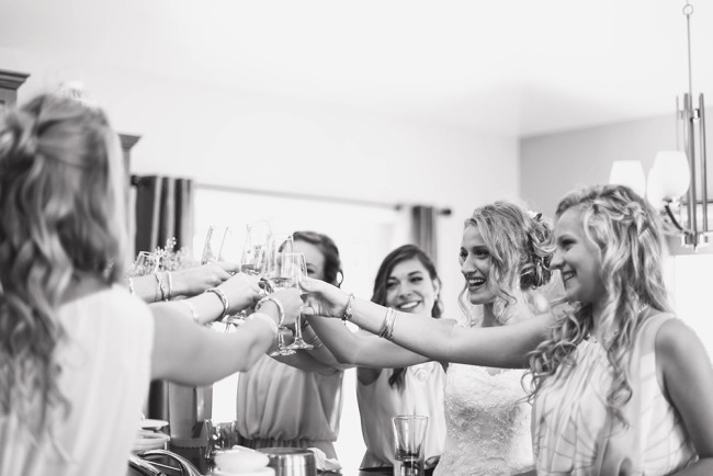 Black and white photo of a bride toasting with champagne to her bridesmaids