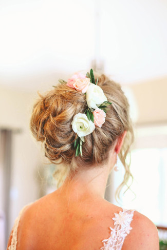 Bride hair in a messy bun with fresh flowers
