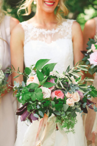 Bride carrying a beautiful loose bouquet of pink and peach roses and greenery