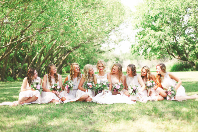 Bride sitting on the grass with bridesmaids holding peach and pink bouquets