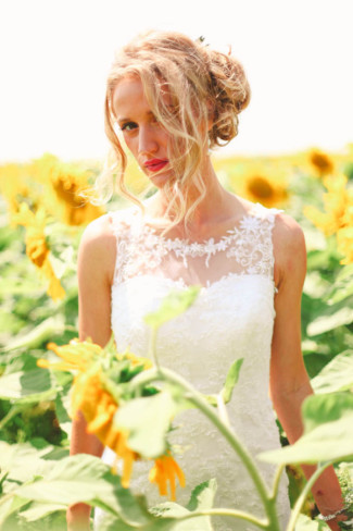 Bride standing in a field of sun flowers
