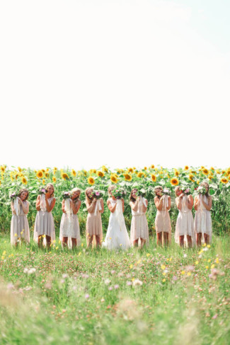 Bride with bridal party holding up their bouquets in front of sun flowers
