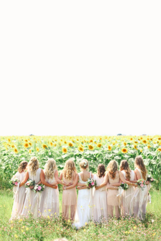 Bride standing with bridesmaids in a field of sun flowers