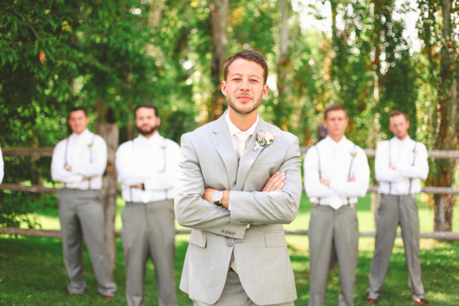 Groom in grey suit standing with groomsmen wearing suspenders