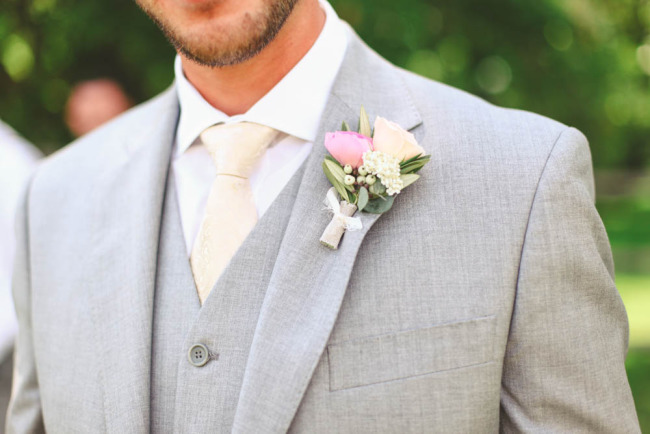 Groom wearing grey suit with pink tie and pink boutonniere
