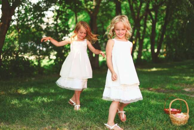 Flower girls wearing white playing in the grass with wicker flower baskets