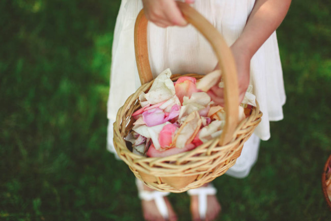 Flower girl holding wicker flower basket with rose petals