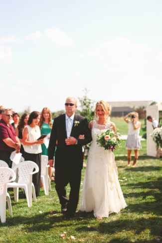 Father walking bride down the aisle in outdoor wedding