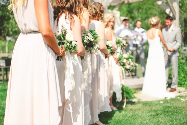 Bridesmaids wearing mismatched blush dresses during wedding ceremony
