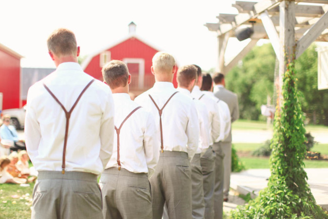 groomsmen lined up during wedding ceremony wearing grey pants and brown suspenders