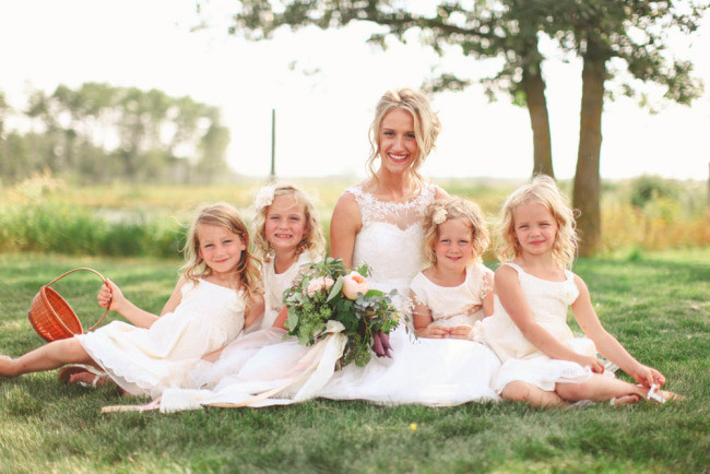 Bride sitting in the grass with flowers girls