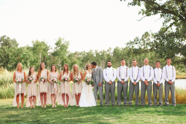Bride and groom kissing lined up with bridal party wearing grey and blush pink