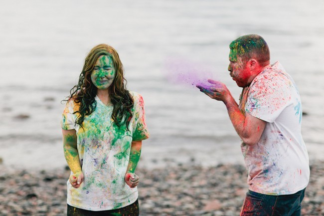 A man blowing holi powder on his fiancee standing on a beach