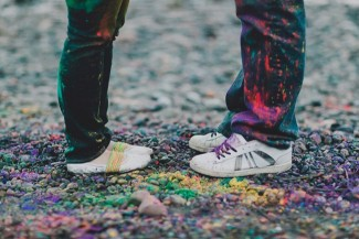 A photo of a couple standing on a rocky beach towards each other covered in holi powder