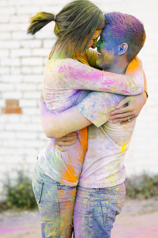 A guy picking up his fiancee after a holi powder fight