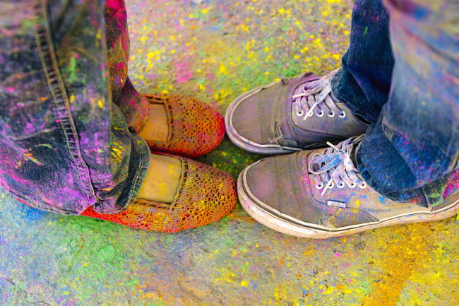 2 pairs of legs standing toe to toe covered in holi powder