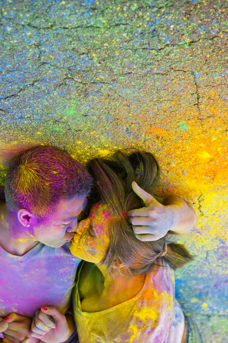 A couple kissing on the cement after a holi powder fight