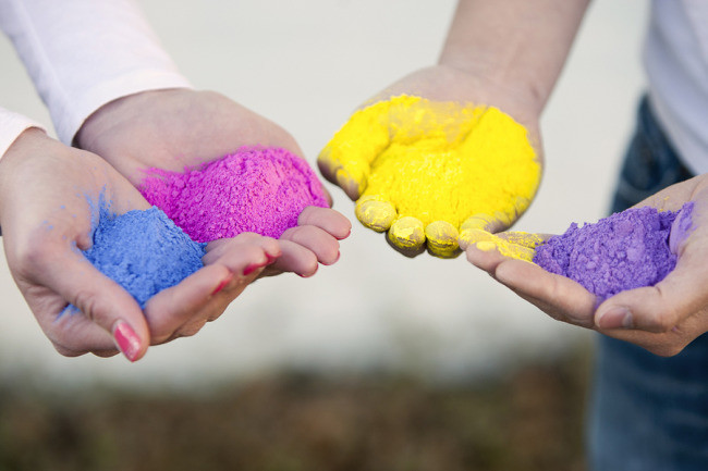 4 hands holding out colorful holi powder