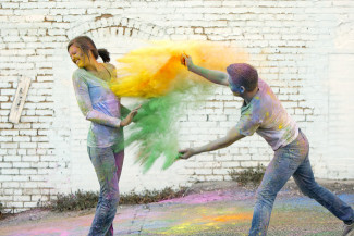 A guy throwing holi powder at his fiancee during an engagement session