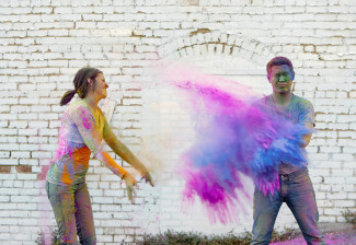 A girl throwing holi powder at her fiancee for their engagement session