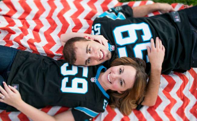 Engagement photos of a couple laying on an red chevron pattern blanket wearing jerseys