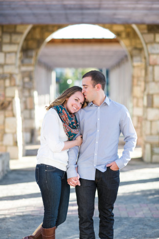 Engagement photos of a couple standing under an arch with guy kissing girls head