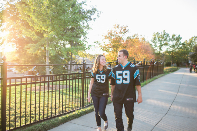 Couple walking holding hands wearing Carolina Panther jerseys for engagement photos